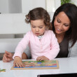 Little girl and woman doing puzzle — Stock Photo #8470270