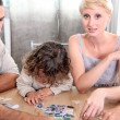 Stock Photo: A family making a jigsaw puzzle.