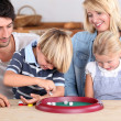 Family playing a dice game — Stock Photo #8470367