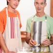 A young man and an old man making a cake — Stock Photo #8470379