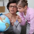 Little girl looking at a globe with her grandmother - Stock Photo