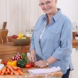 Older woman chopping vegetables — Stock Photo