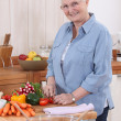 Older woman chopping vegetables - Stock Photo