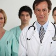 A doctor and three nurses behind him, all looking at us. — Stock Photo #8471056