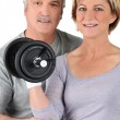 Older couple using gym weights — Stock Photo