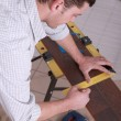 Man measuring wood flooring - Stock Photo