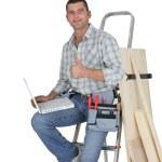 Carpenter ordering stock on-line — Stock Photo