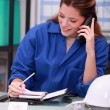 Woman wearing blue overalls speaking on telephone — Stock Photo