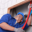 Plumber feeding flexible pipes behind a tiled wall — Stock Photo #8473921