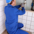 Stock Photo: Plumber repairing water pipes