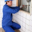 Plumber fixing a pipe to a wall — Stock Photo