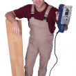 Stock Photo: Joiner with parquet strips and sander machine