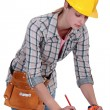 Stock Photo: Female carpenter taking measures.