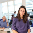 Woman fronting a busy office - Stock Photo
