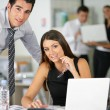 Foto Stock: Couple flirting at work
