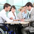 Man in wheelchair with colleagues in a meeting — Stock Photo