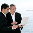 Businessmen outdoors working on laptop — Stock Photo #8475381