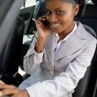 Businesswoman making call whilst sat in car - Stockfoto