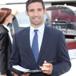 Man in suit taking notes in front of an airplane — Stock Photo