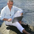 Man using his laptop by the water's edge — Stock Photo #8476127