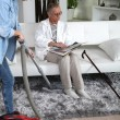 A young woman vacuuming at a senior woman's home - Stockfoto