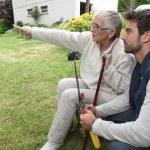 giovane uomo e la donna più anziana in giardino — Foto Stock