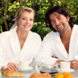 Couple eating breakfast outdoors - Stock Photo