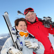 Retired couple having fun on a skiing trip - Stock Photo