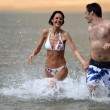Couple running in the water — Stock Photo