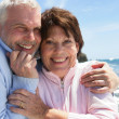 Mature couple hugging by the oceanside - Stock Photo
