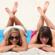 Lazy day on the beach: two girls lying on their stomachs with legs crossed — Stock Photo #8477458