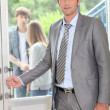 Teacher carrying briefcase opening door — Stockfoto