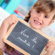 Little girl writing on chalkboard — Zdjęcie stockowe #8477556