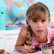 Stock Photo: Little girl drawing with crayons