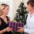 Couple with a Christmas present — Stock Photo