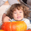 Royalty-Free Stock Photo: A plump kid carving a pumpkin.