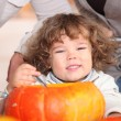 Stock Photo: Plump kid carving pumpkin.