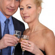 图库照片: Mature couple toasting with champagne.