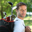 Golfer carrying clubs — Stock Photo #8477796