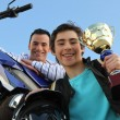 Father and son holding trophy after motorbike race — Stock Photo