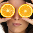 Hiding her eyes with oranges — Stock Photo
