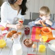 Mother and son eating breakfast at the table — Stock Photo #8478302