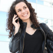 Stock Photo: Womwearing leather jacket and talking on phone