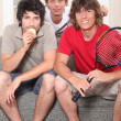 Guys sitting on sofa with tennis rackets — Stock Photo