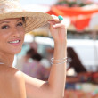 Woman wearing straw hat stood by outdoor market — Stock Photo