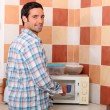 Man putting cup in microwave — Stock Photo