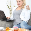 Young blonde working on laptop while having breakfast — Stock Photo