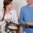 A young couple making crepes. — Stock Photo