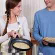 A young couple making crepes. — Lizenzfreies Foto