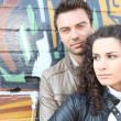 Couple stood by wall covered in graffiti - Stock Photo